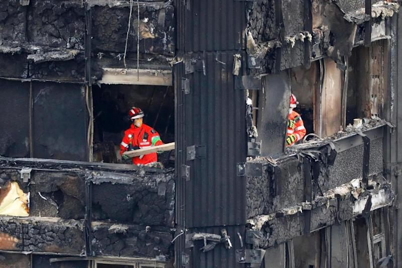 Recovery: Members of the emergency services in the middle floors over the weekend. (AFP/Getty Images)