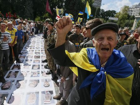 """People protest near a """"corridor of shame"""" made up of portraits of Ukrainian deputies from the Party of Regions and Communist Party laid out on the ground to press demands for parliament to be dissolved and early elections outside the assembly at the entrance to parliament in Kiev June 17, 2014. REUTERS/Gleb Garanich"""