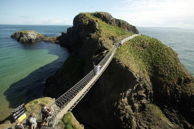 BELFAST, UNITED KINGDOM - JUNE 04: In this handout image provided by LOCOG, Torchbearer Denis Broderick holds the Olympic Flame on the Carrick-a-Rede rope bridge which links the mainland near the village of Ballintoy to the island of Carrickarede in County Antrim on day 17 of the London 2012 Olympic Torch Relay on June 4, 2012 near Belfast, Northern Ireland. The Olympic Flame is now on day 17 of a 70-day relay involving 8,000 torchbearers covering 8,000 miles. (Photo by LOCOG via Getty Images)