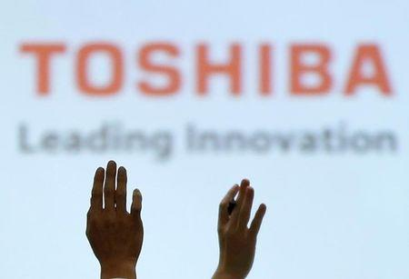 FILE PHOTO -  Reporters raise their hands for a question during a news conference by Toshiba Corp CEO Satoshi Tsunakawa and other senior sompany officials at the company's headquarters in Tokyo, Japan