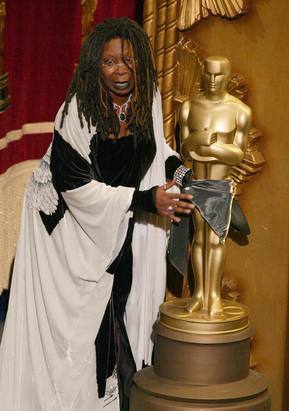 US actress and comedian Whoopi Goldberg jokes around with a Oscar statue during the 74th Academy Awards at the Kodak Theater in Hollywood 24 March 2002. (TIMOTHY A. CLARY/AFP/Getty Images)