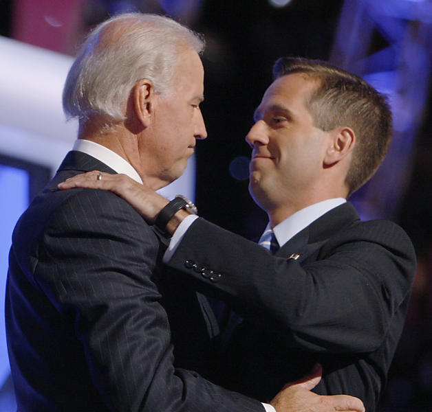 FILE - In this Aug. 27, 2008, file photo, then-Democratic vice presidential candidate Sen. Joe Biden, D-Del., left, embraces his son Beau on stage at the Democratic National Convention in Denver. A spokesman for the Delaware Department of Justice says Beau Biden, that state's attorney general, has been hospitalized after becoming weak and disoriented after a drive for a family vacation. Agency spokesman Jason Miller said late Monday that Biden, the vice president's son, is currently undergoing testing in Houston to investigate the cause of his symptoms. Vice President Biden accompanied his son to Houston. (AP Photo/Charles Dharapak, File)