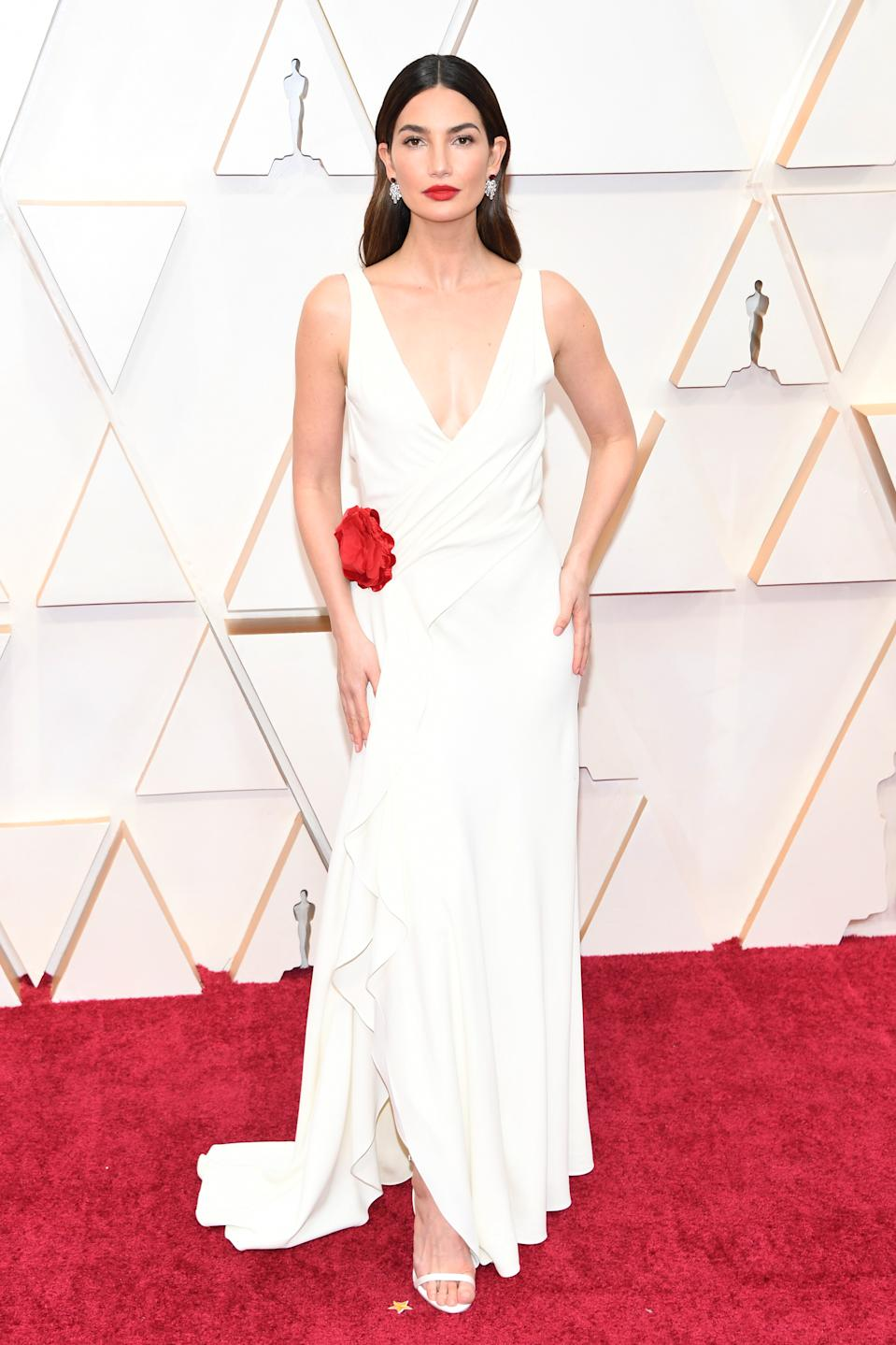 Aldridge looked angelic in a white gown by Ralph Lauren that featured a pop of colour in a red silk rosette at the hip. The model completed the look with diamond and ruby earrings and a bold red lip.
