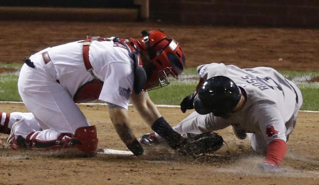 Boston Red Sox's David Ross is tagged out at home by St. Louis Cardinals catcher Yadier Molina during the seventh inning of Game 5 of baseball's World Series Monday, Oct. 28, 2013, in St. Louis. (AP Photo/Charlie Riedel)