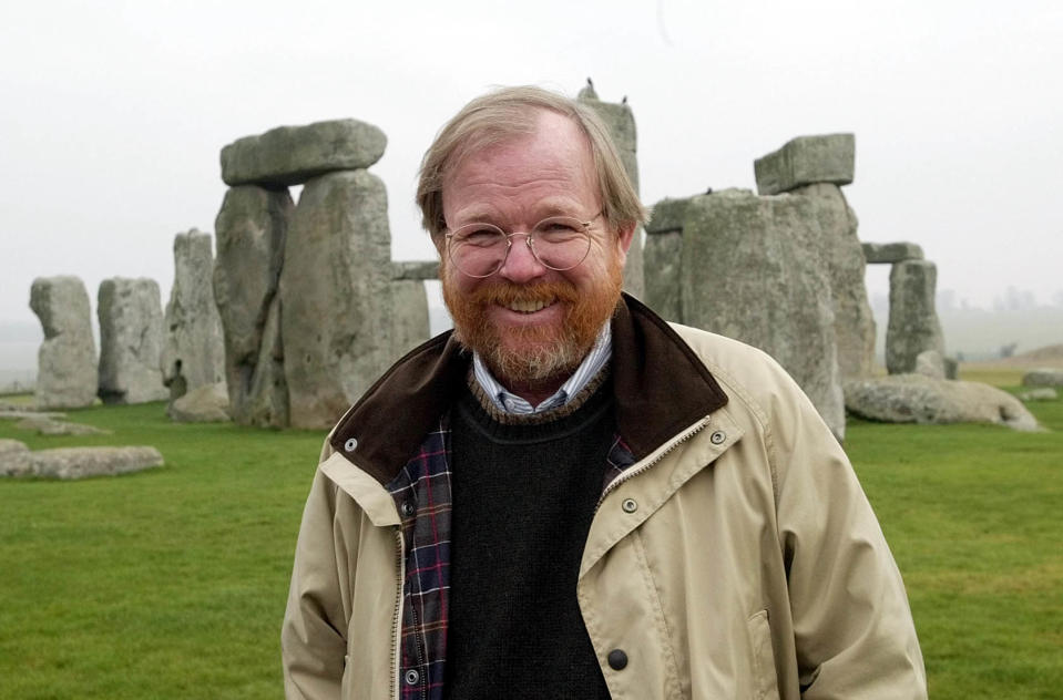 """American author Bill Bryson, poses at Stonehenge, the stone circle, near Salisbury in Wiltshire,England, Friday, Dec.19, 2003. Bryson has been recently appointed an English Heritage Commisioner and his brief is to make the historic site more accessible and increase visitor access. His non-fiction """"A Short History of Nearly Everything,'' is currently on best seller lists. (AP Photo/Dave Caulkin)"""