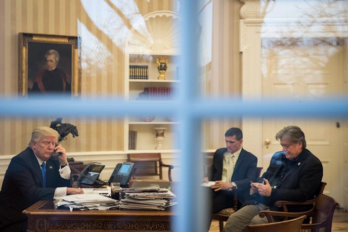 President Donald Trump speaks on the phone with Australian Prime Minister Malcolm Turnbull in the Oval Office of the White House, January 28, 2017 in Washington, DC. Also pictured at right, National Security Advisor Michael Flynn and White House Chief Strategist Steve Bannon.