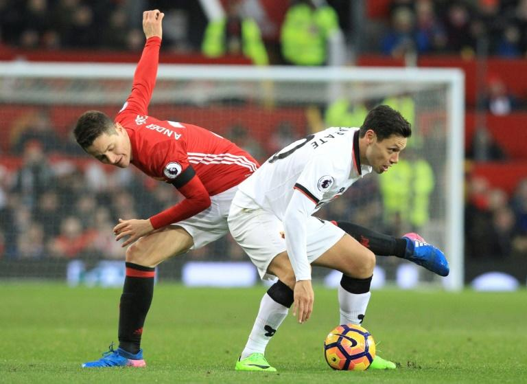Manchester United's midfielder Ander Herrera (L) challenges Watford's midfielder Mauro Zarate (R) during the English Premier League football match February 11, 2017