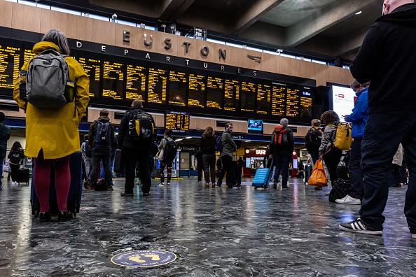 Commuters in protective face masks are seen at Euston Station waiting for their trains and observing social distancing in London, England.