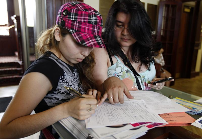 Applicant Laura Sanchez, from Mexico, left, fills the Casa de Maryland registration form, with help of her sister Nancy, before they can apply this afternoon for the Deferred Action Childhood Arrivals, Wednesday, Aug. 15, 2012, at Casa de Maryland in Langley Park, Md. Hundreds of thousands of young illegal immigrants scrambled to get papers in order Wednesday as the U.S. started accepting applications to allow them to avoid deportation and get a work permit _ but not a path to citizenship. (AP Photo/Jose Luis Magana)
