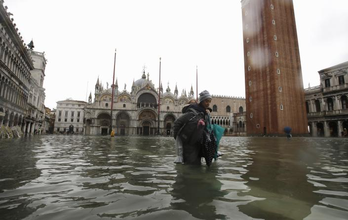 A woman carries her daughter in a flooded St. Mark's Square, in Venice, Italy, Tuesday, Nov. 12, 2019. (Photo: Luca Bruno/AP)