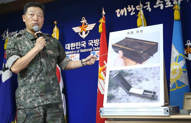 """A South Korean military officer shows pictures of North Korean """"wooden box"""" land mines during a briefing at the Defence Ministry in Seoul on August 10, 2015"""