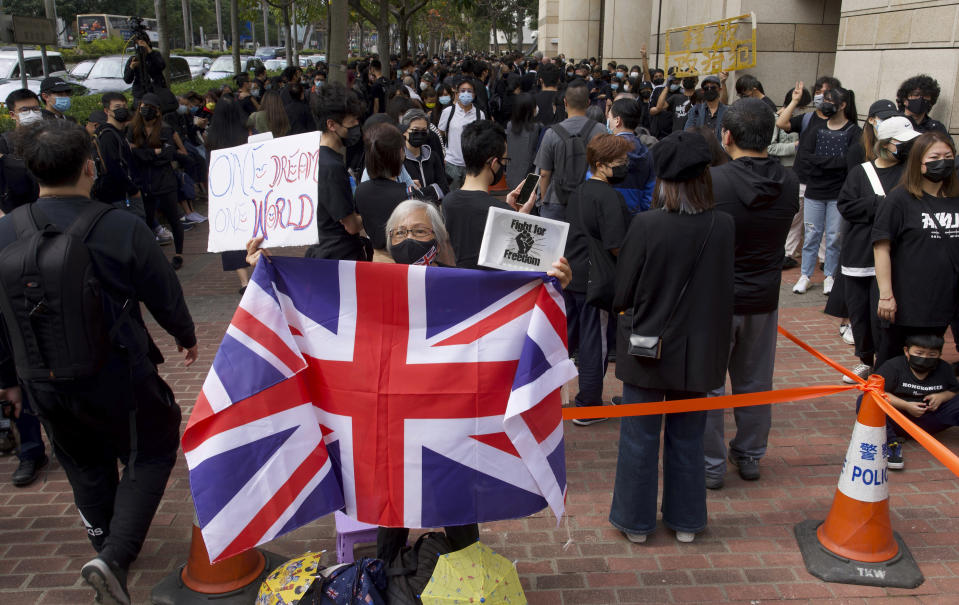 A woman holds a British flag as supporters queue up outside a court to try get in for a hearing in Hong Kong Monday, March 1, 2021. People gathered outside the court Monday to show support for 47 activists who were detained over the weekend under a new national security law that was imposed on the city by Beijing last year. (AP Photo/Vincent Yu)