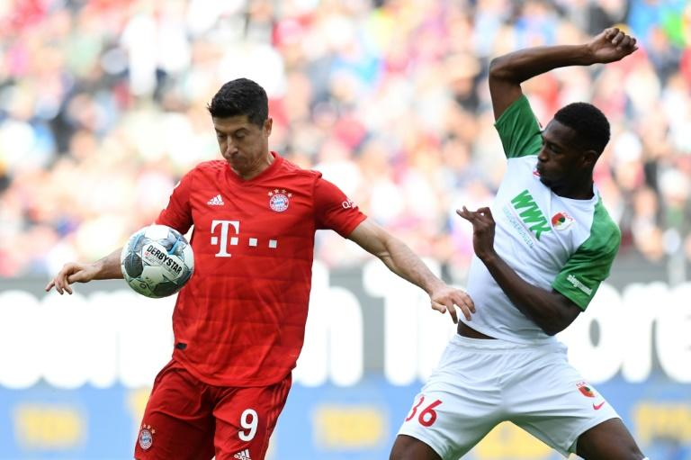 Robert Lewandowski (L) holds off Augsburg's English defender Reece Oxford - the Polish striker scored for Bayern but the Bundesliga champions were held to a 2-2 draw in the Bavarian derby (AFP Photo/Christof STACHE)