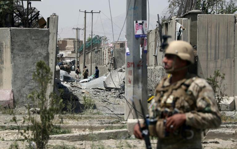 An Afghan security officer stands guard at the site where a Taliban car bomb detonated at the entrance of a police station in Kabul in August 2019