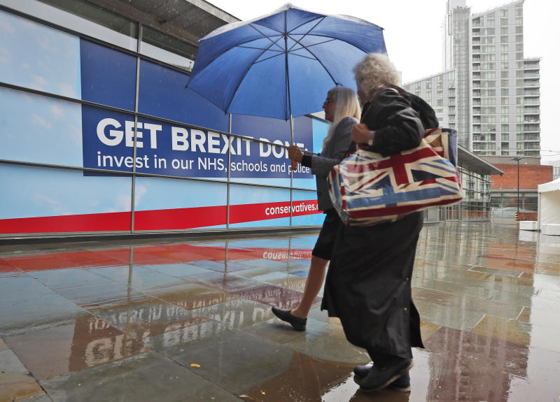 Delegates arrive in heavy rain at the Conservative Party Conference in Manchester, England, Tuesday, Oct. 1, 2019. Britain's Prime Minister Boris Johnson said Tuesday that his government prepared at last to make firm proposals for a new divorce deal with the European Union. Britain is due to leave the 28-nation bloc at the end of this month, and EU leaders are growing impatient with the U.K.'s failure to set out detailed plans for maintaining an open border between Northern Ireland and Ireland — the key sticking point to a deal. (AP Photo/Frank Augstein)