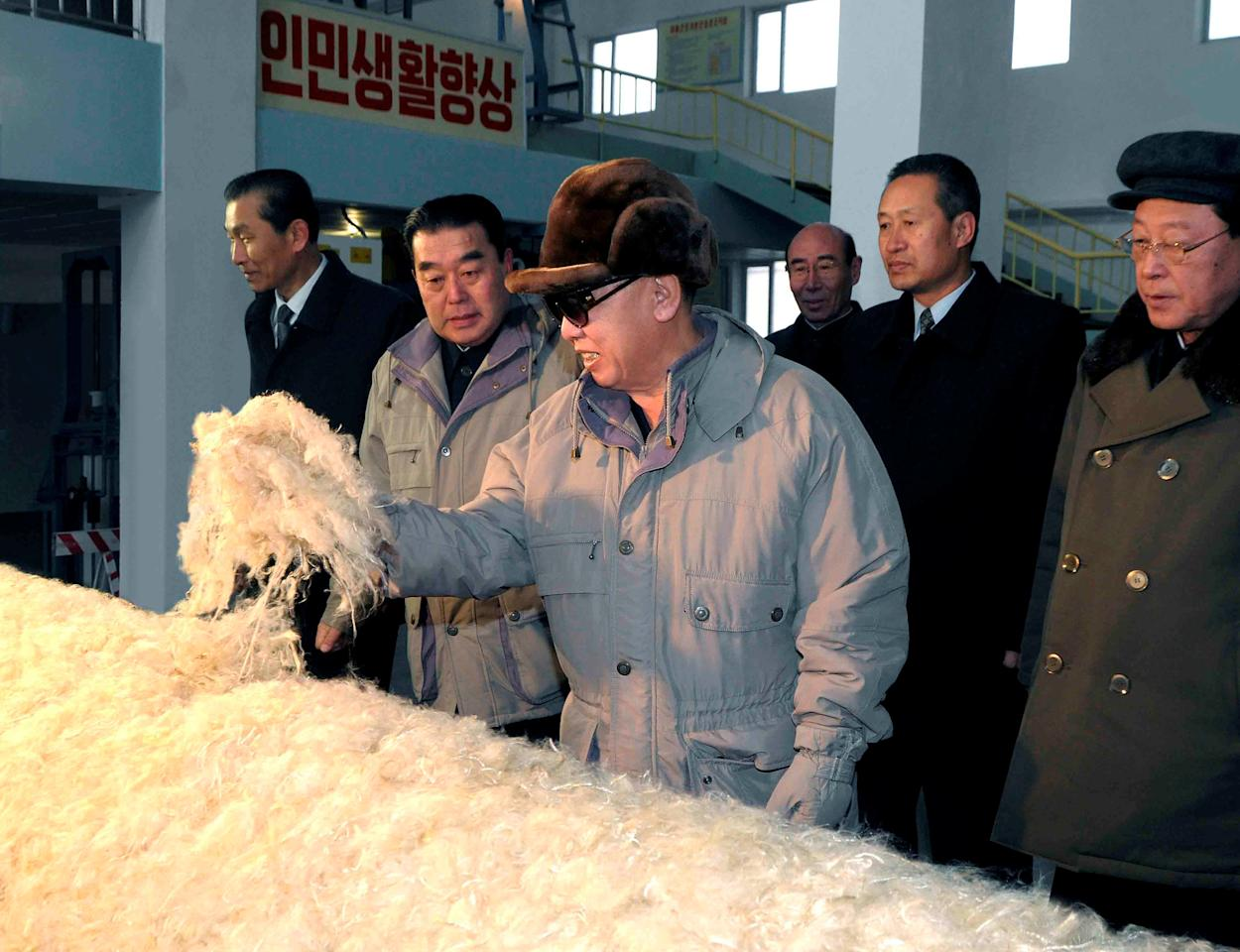 "FILE PHOTO: North Korean leader Kim Jong-il (C) visits the February 8 Vinalon Complex in Hamheung, northeast of Pyongyang in this photo released by North Korea's KCNA news agency February 10, 2010. KCNA did not state when the picture was taken. The Korean characters read: ""Improvement of people's lives"".    To match Special Report NORTHKOREA-VINALON/  REUTERS/KCNA/File Photo ATTENTION EDITORS - THIS IMAGE WAS SUPPLIED BY A THIRD PARTY. NO THIRD PARTY SALES. NOT FOR USE BY REUTERS THIRD PARTY DISTRIBUTORS. QUALITY FROM SOURCE. SOUTH KOREA OUT."