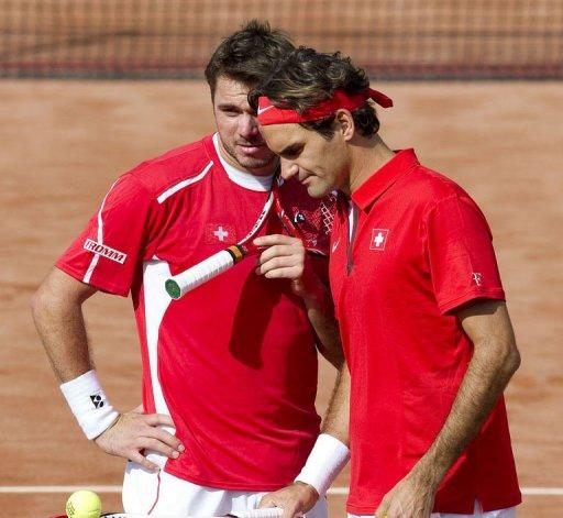Switzerland's Roger Federer (R) and Stanislas Wawrinka speak during the Davis Cup World Group play-off doubles match against Netherlands' Jean-Julien Rojer and Robin Haase in Amsterdam. Netherlands won the match
