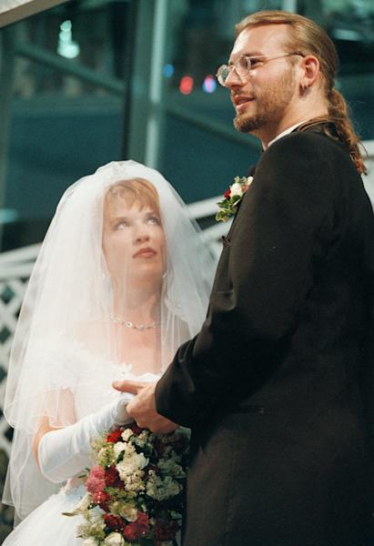"""FILE - In this June 13, 1998 file photo, Elizabeth Runze looks up as David Weinlick says, """"I do"""" during their wedding ceremony at Mall of America in Bloomington, Minn. Weinlick's family and friends picked Runze from a group of 23 possible brides less than two hours before the wedding. The Minnesota couple who began their life together through an arranged marriage nearly 20 years ago are about to renew their vows. The ceremony on Friday, Aug. 18, 2017 will again be at the Mall of America. (AP Photo/Scott Cohen File)"""