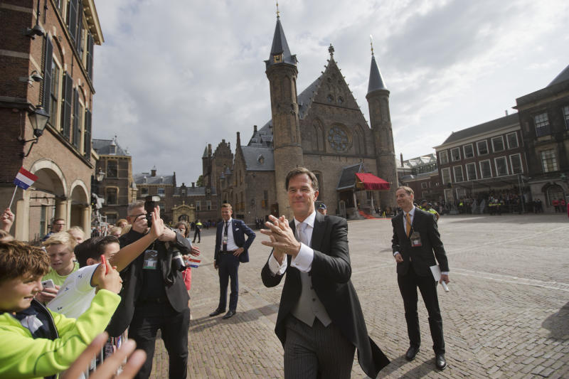 Dutch Prime Minister Mark Rutte greets children as he arrives at the Knight's Hall, rear, in The Hague, Netherlands, Tuesday, Sept. 17, 2019, for a ceremony marking the opening of the parliamentary year with a speech by King Willem-Alexander outlining the government's budget plans for the year ahead. (AP Photo/Peter Dejong)