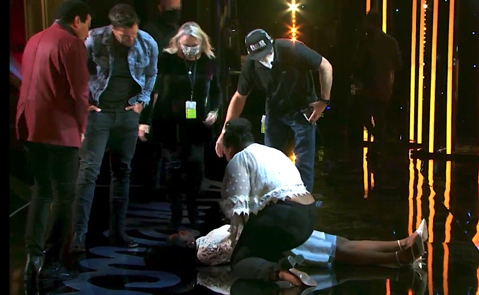 Concerned judges Lionel Richie and Luke Bryan check on contestant Funke Lagoke after she faints onstage during Hollywood Week. (Photo: ABC)
