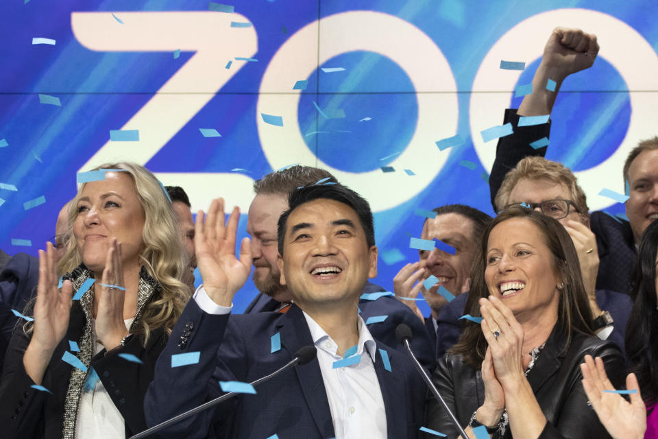 Zoom CEO Eric Yuan, center, celebrates the opening bell at Nasdaq as his company holds its IPO, Thursday, April 18, 2019, in New York. The videoconferencing company is headquartered in San Jose, California. (AP Photo/Mark Lennihan)