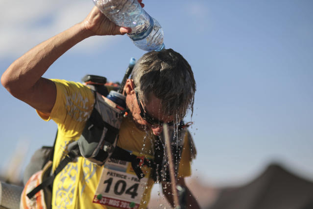 A competitor cools down at a checkpoint while taking part in stage 4 of the 33rd edition of Marathon des Sables, in the Sahara desert, near Merzouga, southern Morocco, Wednesday, April 11, 2018. Under a hot desert sun and with the desolation of the Sahara all around, about 1,000 competitors from 50 countries took part in this year's Marathon des Sables, or Marathon of the Sands. (AP Photo/Mosa'ab Elshamy)