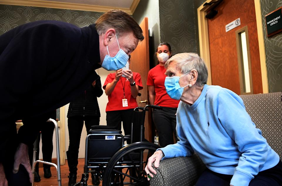 Governor Ned Lamont greets Jeanne Peters, 95, a rehab patient at The Reservoir, a nursing facility, after she was given the first coronavirus disease (COVID-19) vaccination at the nursing home, in West Hartford, Connecticut, U.S., December 18, 2020. Stephen Dunn/Pool via REUTERS