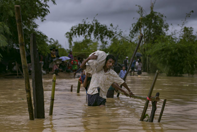 <p>Refugees cross a flooded bridge in the Balukhali Rohingya refugee camp on Sept. 19, 2017 in Cox's Bazar, Bangladesh. (Photo: Allison Joyce/Getty Images) </p>