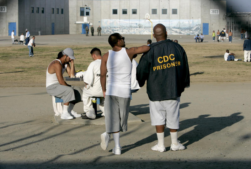 FILE - In this Jan. 14, 2009 file photo inmates use the recreation yard at Corcoran State Prison in Corcoran, Calif.  California prison officials have halted an experiment aimed at trying to force warning prison gangs to get along with each other. Officials tell The Associated Press the temporary halt came after the inmates wound up brawling and even rioting after they were allowed to mingle together in prison recreation yards. The effort started more than a year ago with officials allowing prisoners from the different gangs into exercise yards to try to get them to interact and make peace.  (AP Photo/Rich Pedroncelli, File )