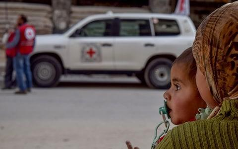 <span>A Syrian girl sits on the floor as United Nations' aid convoy enters the Douma town of Eastern Ghouta</span> <span>Credit: Getty </span>