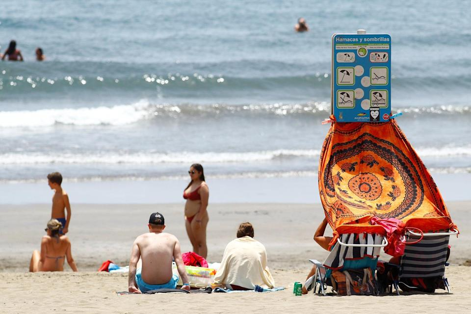 Tourists sit in Playa del Ingles in the south of the island of Gran Canaria, Spain (Reuters)