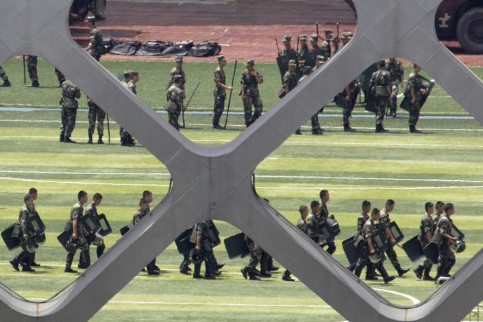 Chinese paramilitary policemen go through drills at the Shenzhen Bay Stadium in Shenzhen in Southern China's Guangdong province, Sunday, Aug. 18, 2019. Members of China's paramilitary People's Armed Police force have been training for days across the border in Shenzhen, including on Sunday morning, fueling speculation that they could be sent in to suppress the protests. The Hong Kong police, however, have said they are capable of handling the protests. (AP Photo/Ng Han Guan)