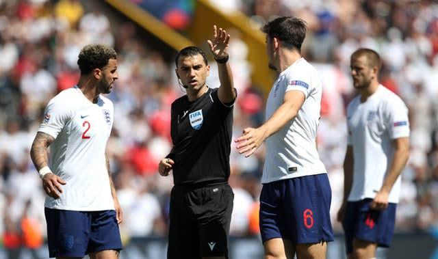 Harry Maguire and Kyle Walker exchange words with match referee Ovidiu Hategan (Tim Goode/PA)
