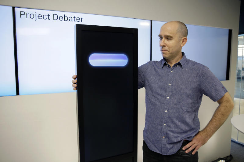 "FILE - In this Monday, June 18, 2018 file photo, Dr. Noam Slonim, principal investigator, stands with the IBM Project Debater before a debate between the computer and two humans in San Francisco. Slonim put humor into the programming, figuring that a one-liner every now could help in a debate. But in initial internal tests, it backfired when the system gave a humorous remark at an inappropriate time and way. ""We know that humor _ at least good humor _ relies on nuance and on timing,"" Slonim said. ""And these are very hard to decipher by an automatic system."" (AP Photo/Eric Risberg)"