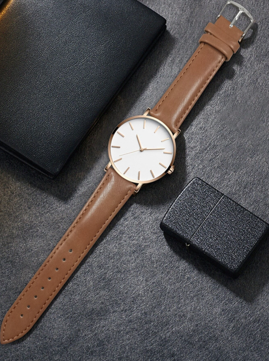 men's brown leather watch with white face and rose gold details laying flat