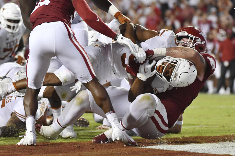 Texas running back Bijan Robinson (5) pushes past Arkansas defensive lineman John Ridgeway (99) to score a touchdown in the second half of an NCAA college football game Saturday, Sept. 11, 2021, in Fayetteville, Ark. (AP Photo/Michael Woods)