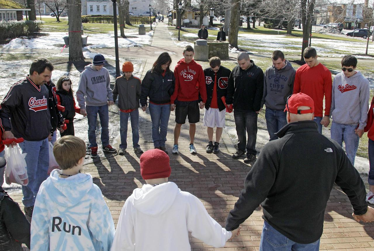 A group of students and parents pray for victims of a school shooting on the square in Chardon, Ohio Tuesday, Feb. 28, 2012. A gunman opened fire inside the Chardon High School cafeteria at the start of the school day Monday. Two of the victims have died and wounding three remain hospitalized. (AP Photo/Mark Duncan)