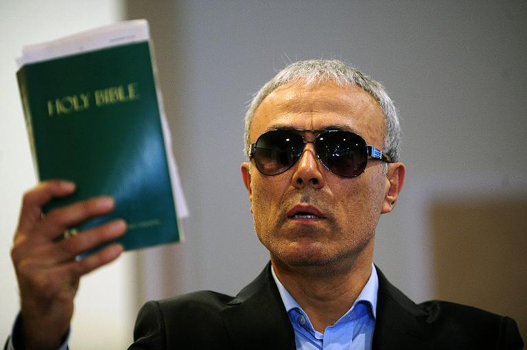 Mehmet Ali Agca, the Turkish man who attempted to assassinate Pope John Paul II in 1981, holds a copy of the Bible during a press conference in Istanbul on November 27, 2014