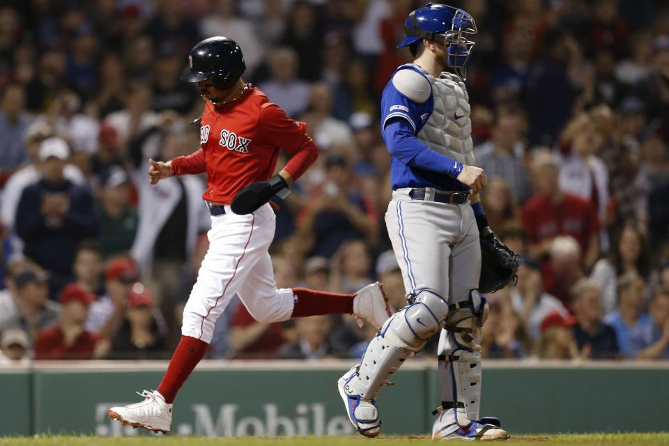 Boston Red Sox's Mookie Betts, left, scores behind Toronto Blue Jays' Danny Jansen on a single by Andrew Benintendi during the seventh inning of a baseball game in Boston, Friday, June 21, 2019. (AP Photo/Michael Dwyer)