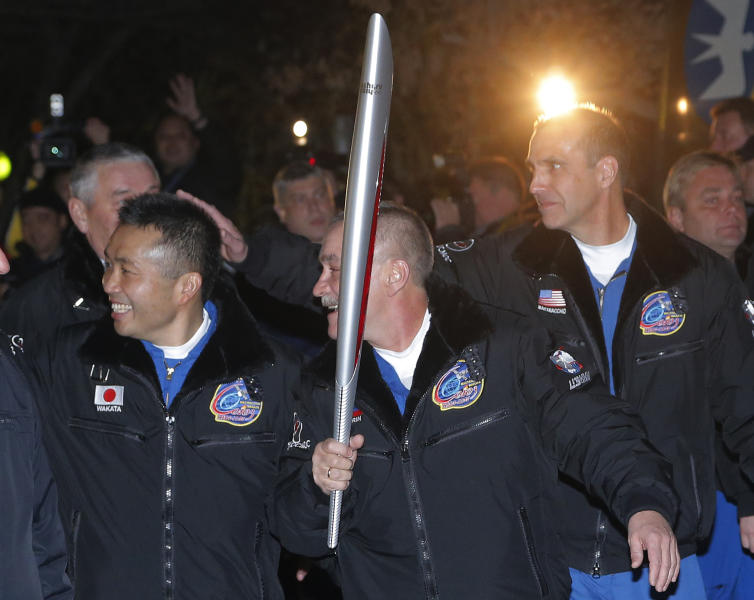 From left, Japanese astronaut Koichi Wakata, Russian cosmonaut Mikhail Tyurin and U.S. astronaut Rick Mastracchio, crew members of the mission to the International Space Station (ISS) walk to a bus from a hotel with an Olympic torch prior the launch of a Soyuz-FG rocket at the Russian leased Baikonur cosmodrome, Kazakhstan, Thursday, Nov. 7, 2013. The crew will deliver Olympic torch to space as part of the ongoing Olympic torch relay. The torch will be brought back along with the station's current crew. (AP Photo/Dmitry Lovetsky)