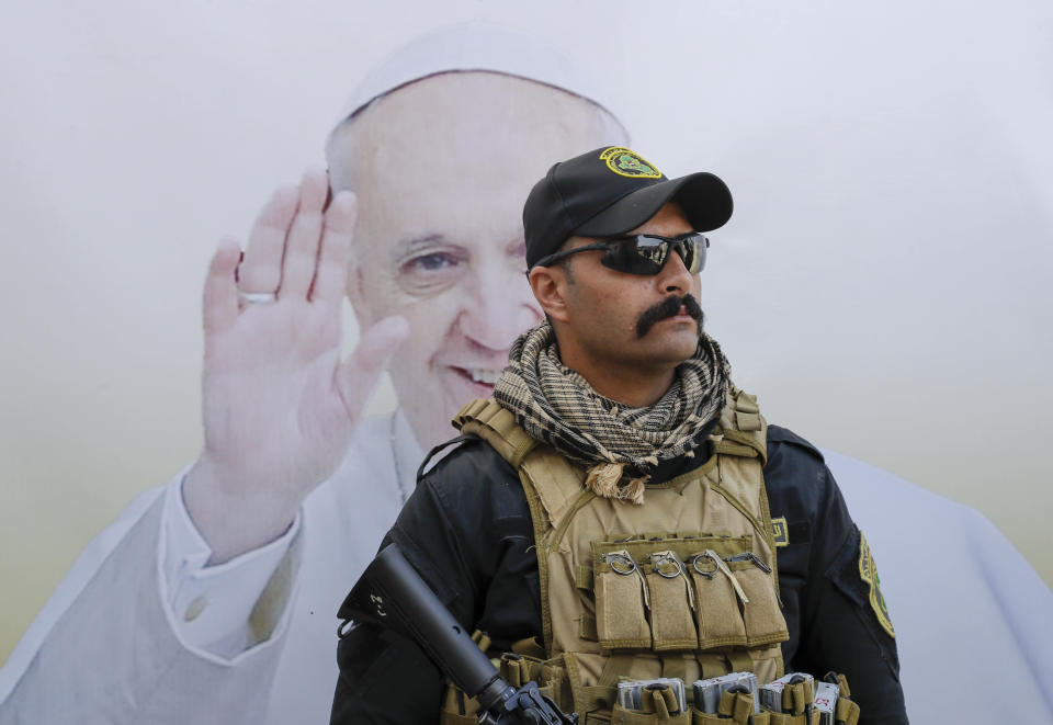 An Iraqi security officer follows the prayer session led by Pope Francis for the victims of war at Hosh al-Bieaa Church Square, in Mosul, Iraq, once the de-facto capital of IS, Sunday, March 7, 2021. The long 2014-2017 war to drive IS out left ransacked homes and charred or pulverized buildings around the north of Iraq, all sites Francis visited on Sunday. (AP Photo/Andrew Medichini)