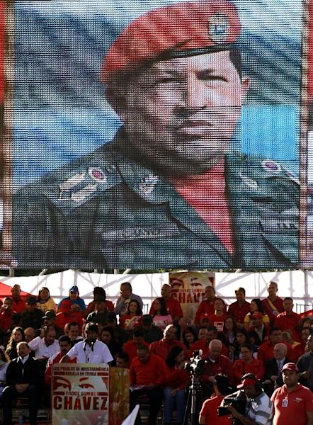 An image of Venezuela's President Hugo Chavez is shown on a large screen as Bolivia's President Evo Morales, bottom left, speaks to the crowd attending Chavez's symbolic inauguration outside Miraflores presidential palace in Caracas, Venezuela, Thursday, Jan. 10, 2013. The government organized the unusual show of support for the cancer-stricken leader on the streets outside Miraflores Palace on what was supposed to be his inauguration day. The Venezuelan leader, normally at the center of national attention, is so ill following a fourth cancer surgery in Cuba that he has made no broadcast statement in more than a month, and has not appeared in a single photo. Officials have not specified what sort of cancer he suffers or which hospital is treating him. (AP Photo/Fernando Llano)