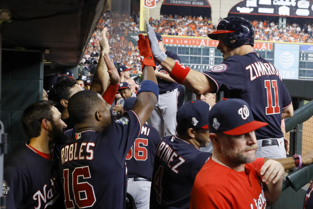 Washington Nationals' Ryan Zimmerman celebrates in the dugout after his home run during the second inning of Game 1 of the baseball World Series against the Houston Astros Tuesday, Oct. 22, 2019, in Houston.(AP Photo/Matt Slocum)
