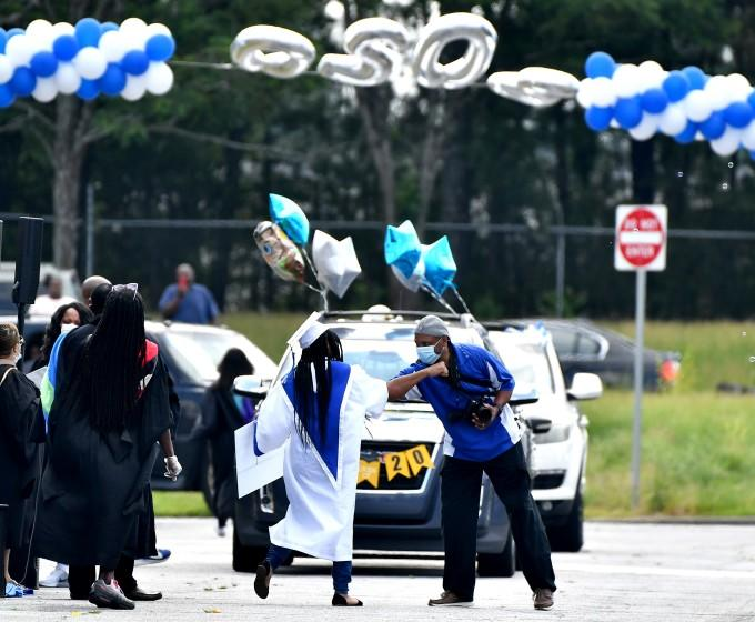 "Students at North Clayton High School in College Park, Ga., take part in a drive-through commencement in June. <span class=""copyright"">(Paras Griffin / Getty Images,)</span>"