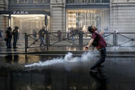 A demonstrator reacts as police fire teargas during a protest, in Rome, Saturday, Oct. 9, 2021. Thousands of demonstrators protested Saturday in Rome against the COVID-19 health pass that Italian workers, both the public and private sectors, must display to access their workplaces from Oct. 15 under a government decree. (Cecilia Fabiano/LaPresse via AP)