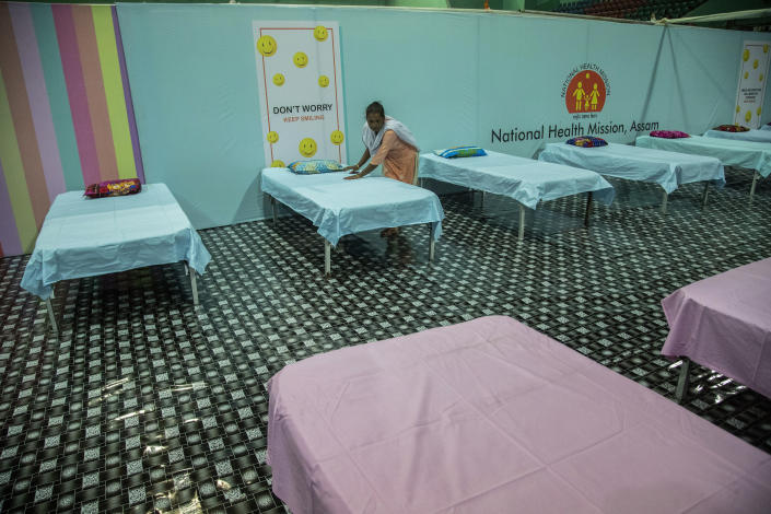 A worker arranges beds at a COVID-19 treatment facility newly set up at an indoor stadium in Gauhati, India, Monday, April 19, 2021. India's health system is collapsing under the worst surge in coronavirus infections that it has seen so far. Medical oxygen is scarce. Intensive care units are full. Nearly all ventilators are in use, and the dead are piling up at crematoriums and graveyards. Such tragedies are familiar from surges in other parts of the world — but were largely unknown in India. (AP Photo/Anupam Nath)