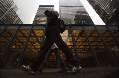 A man walks in front of buildings in the financial district in Toronto