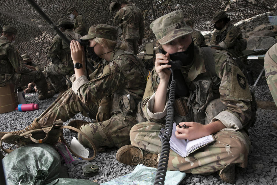 A cadet uses a field radio to call in live fire coordinates, Friday, Aug. 7, 2020, in West Point, N.Y. The pandemic is not stopping their summer training. Cadets had to wear masks this year for much of the training in a wooded area just beyond the main gates of the U.S. Military Academy. (AP Photo/Mark Lennihan)