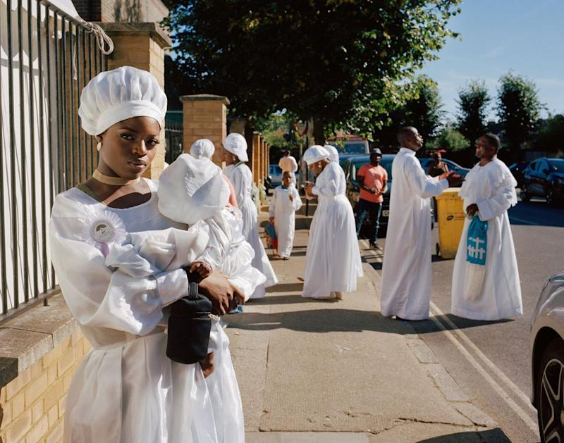 Hannah stands on the street holding her baby cousin whilst members of the Congregation greet each other and chat in the background of the street. | Sophie Green