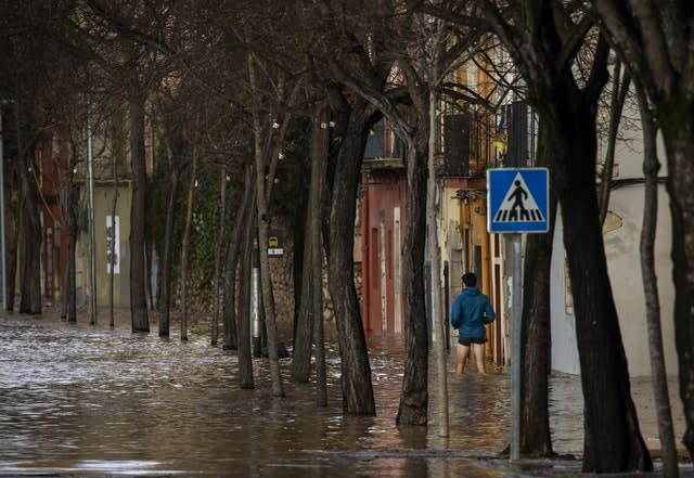 A man walks to his house during flooding following a storm in Girona, Spain